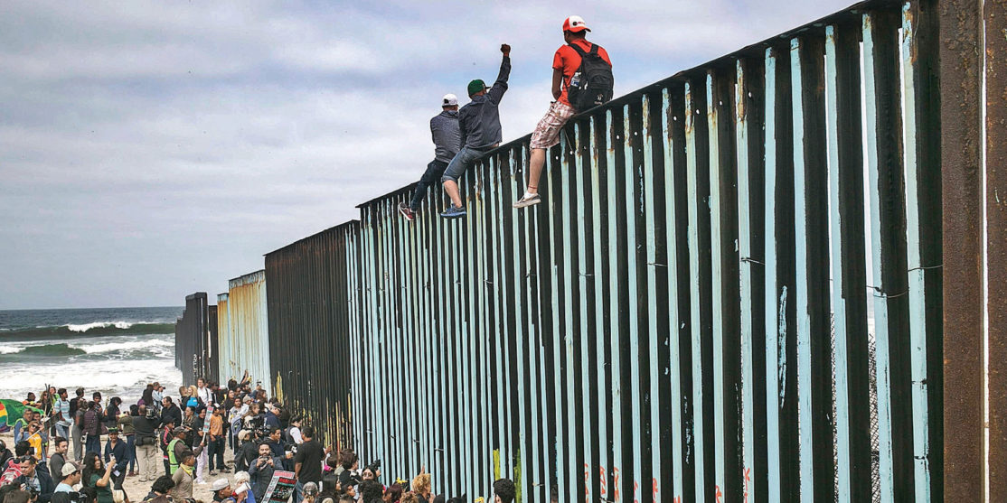 Hundreds of migrants from Central America who traveled as a caravan en masse through Mexico gather with supporters at the border wall in Tijuana, Mexico.