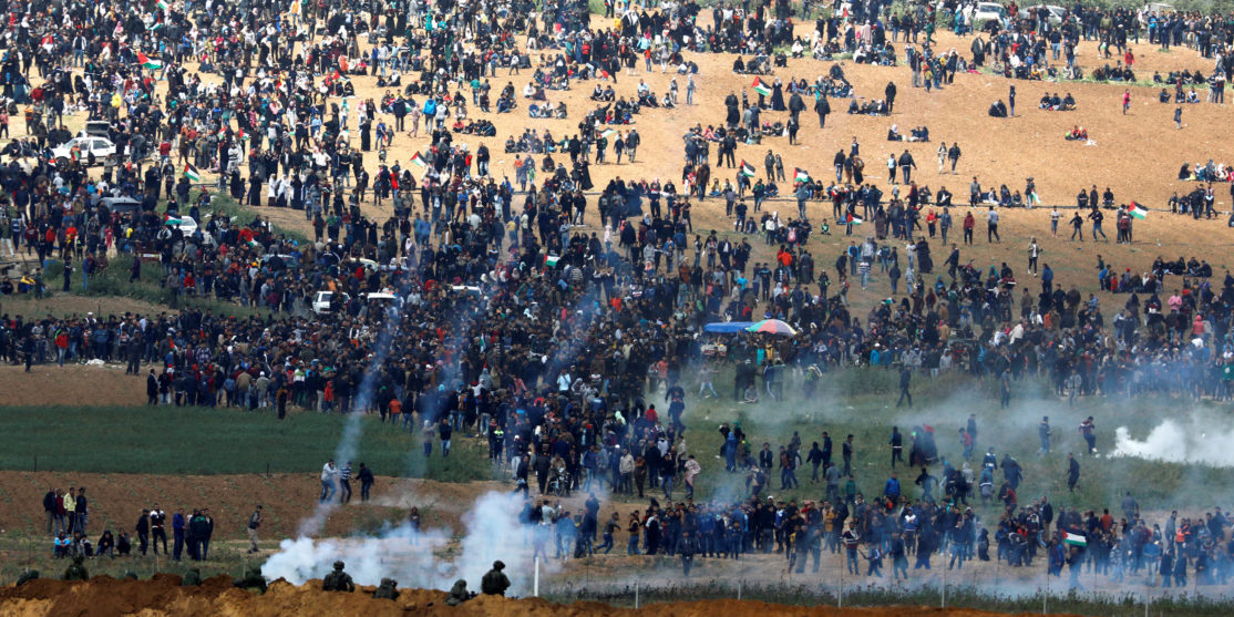 Israeli soldiers shoot tear gas from the Israeli side of the Israel-Gaza border, as Palestinians protest on the Gaza side of the border